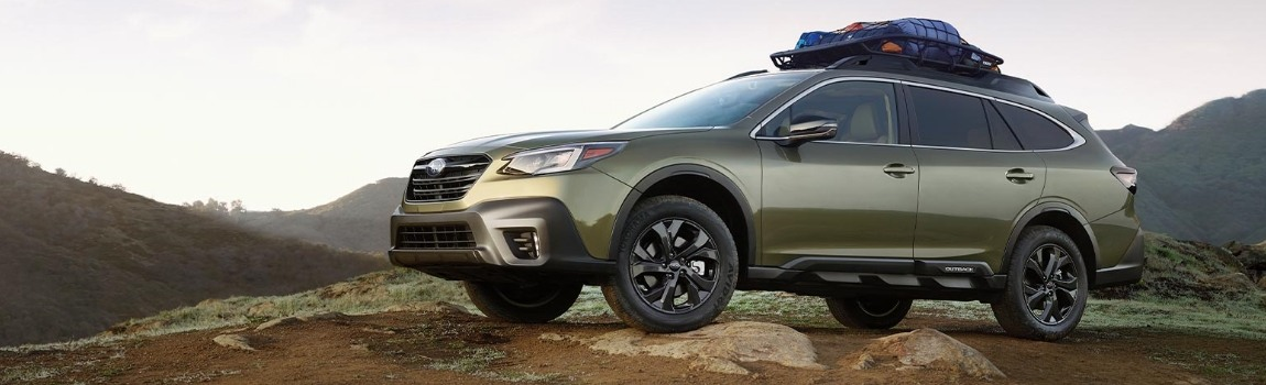 The all-new 2020 Subaru Outback Onyx Edition in Autumn Green Metallic atop a mountain